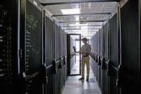 Technician with laptop, checking aisle of server storage cabinets in data center 11080008523| 写真素材・ストックフォト・画像・イラスト素材|アマナイメージズ