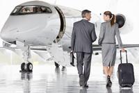 Businesswoman and Businessman walking toward private jet 11080008923| 写真素材・ストックフォト・画像・イラスト素材|アマナイメージズ