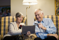 Senior couple using credit card and digital tablet to shop o