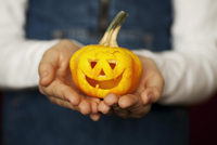 Midsection of girl holding a carved pumpkin
