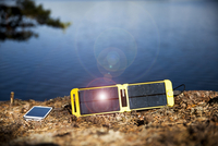 Solar charger and smart phone on lakeshore