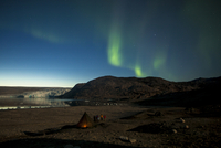 Northern green lights or Aurora Borealis over tent at night
