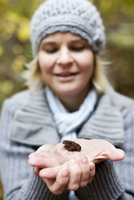 Woman holding frog on palm outdoors