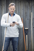 Mature man using smart phone against wooden wall