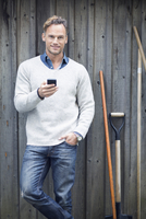 Portrait of mature man using smart phone against wooden wall