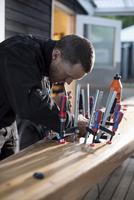 Carpenter fixing clamps on kayak outdoors