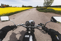 Cropped image of man riding motorcycle on road