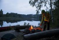 Boy igniting campfire at lakeshore during dusk
