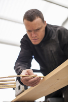 Low angle view of carpenter measuring wooden plank with folding tape at workshop
