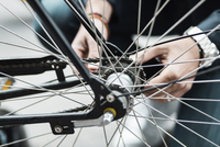 Cropped image of businessman repairing bicycle tire on street