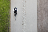 High angle view of businesswoman riding bicycle on road