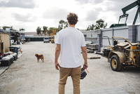 Rear view of carpenter looking at dog while standing outside workshop