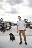 Portrait of carpenter standing with dog outside workshop against sky