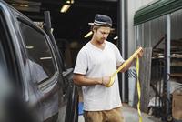 Carpenter rolling measure tape outside workshop