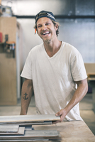 Happy carpenter standing at table in workshop