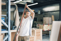Male carpenter carrying wooden plank at workshop