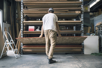 Rear view of man arranging wooden plank in shelf at workshop