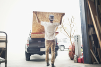 Rear view of man loading wooden planks in pick-up truck