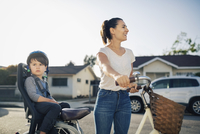 Happy woman looking away while son sitting on bicycle outdoors