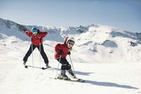 Man with daughter enjoying skiing on snowy mountain