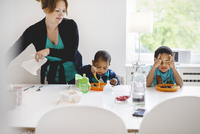 Mother looking at son having food in house 11081006871| 写真素材・ストックフォト・画像・イラスト素材|アマナイメージズ