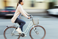 Side view of businesswoman riding bicycle on road