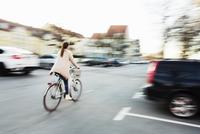 Rear view of businesswoman riding bicycle on city street 11081007004| 写真素材・ストックフォト・画像・イラスト素材|アマナイメージズ
