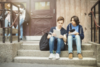 Male teenagers using digital tablet while sitting on steps outdoors