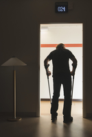 Full length rear view of senior man with crutches in doorway at hospital