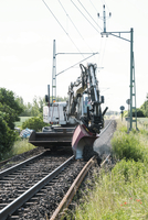 Manual worker operating earth mover on railroad track