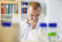 Thoughtful male scientist sitting in laboratory