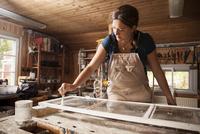 Upholsterer painting window frame at workshop