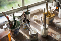 High angle view of paintbrushes and containers on table at workshop