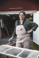 Portrait of smiling female upholsterer outside workshop