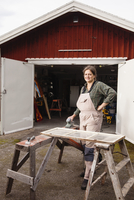 Portrait of confident female upholsterer standing outside workshop