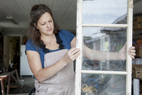 Female upholsterer making window at workshop
