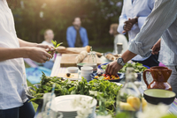 Midsection of friends preparing food at dining table in backyard 11081007430| 写真素材・ストックフォト・画像・イラスト素材|アマナイメージズ