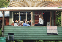 Happy multi-ethnic friends enjoying party in log cabin