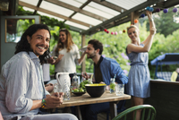 Portrait of happy man sitting at table while enjoying party with friends at summer house