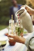 Cropped image of woman serving mojito in bottle at summer party 11081007547| 写真素材・ストックフォト・画像・イラスト素材|アマナイメージズ