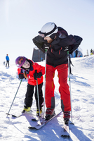 Father and daughter in ski-wear looking at each other while standing on snowcapped mountain