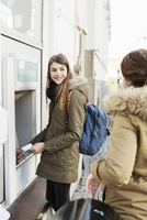 Happy young woman looking at female friend while standing at cash machine