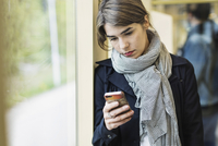 Young woman using mobile phone in tram