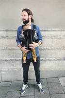 Full length of mid adult father carrying baby in carrier on sidewalk