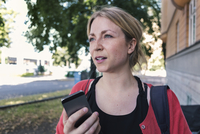 Mid adult woman talking on mobile phone while walking on sidewalk