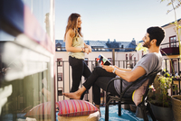 Happy couple planning vacations at balcony