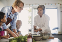 Senior woman teaching family to make Asian food in kitchen