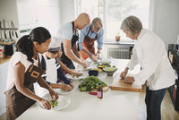 Senior woman in chef's jacket guiding family in preparing Asian food at table in kitchen