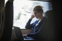 Businesswoman using laptop in train