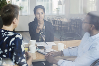 Businesswoman discussing with colleagues at conference table